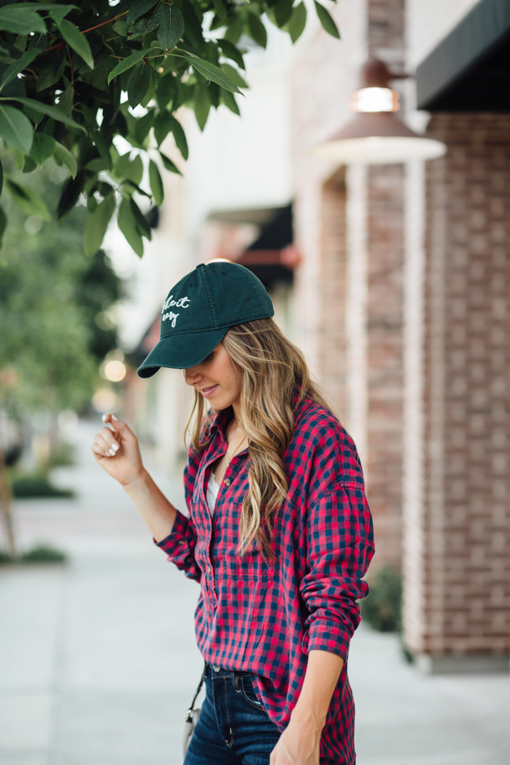 green baseball cap and red plaid shirt