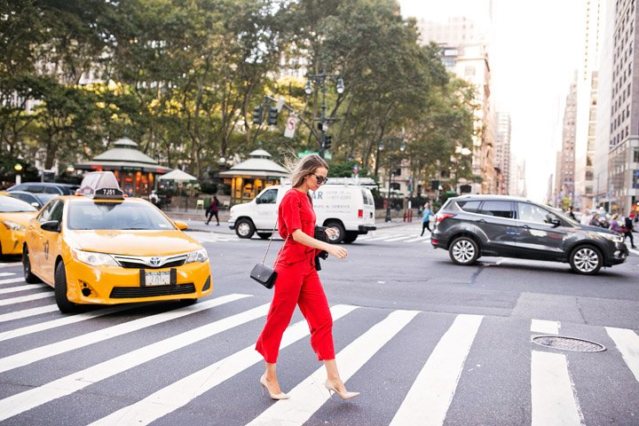 a bold red jumpsuit and nude heels in NYC