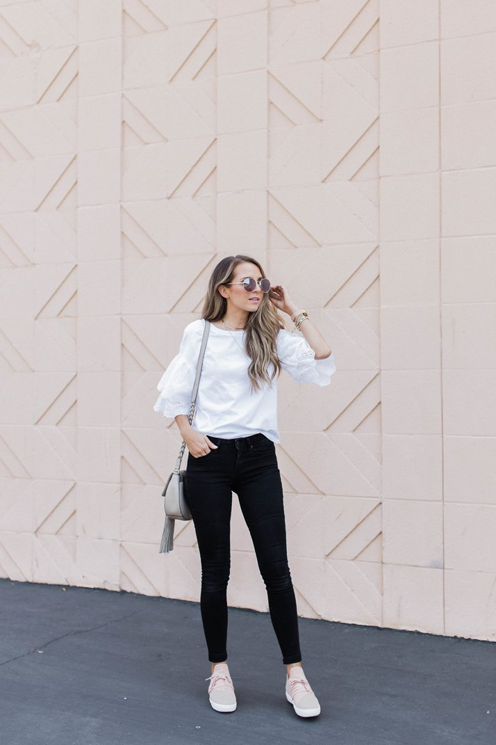 dress down a bold black and white outfit with some blush sneakers