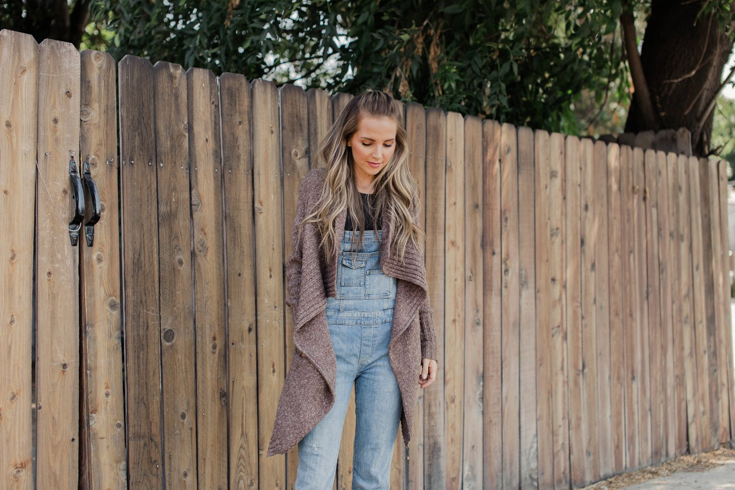 layer your overalls underneath an oversized cardigan sweater for a fall look