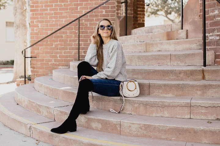 black over the knee boots and a gray sweater