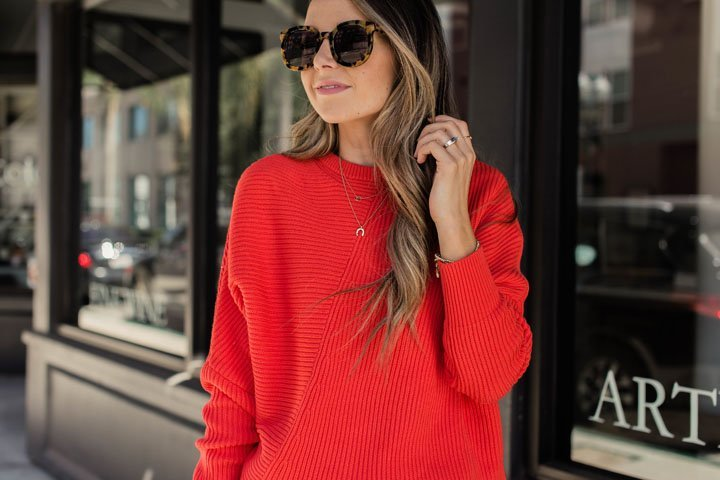 a chunky red sweater and tortoise shell frame glasses