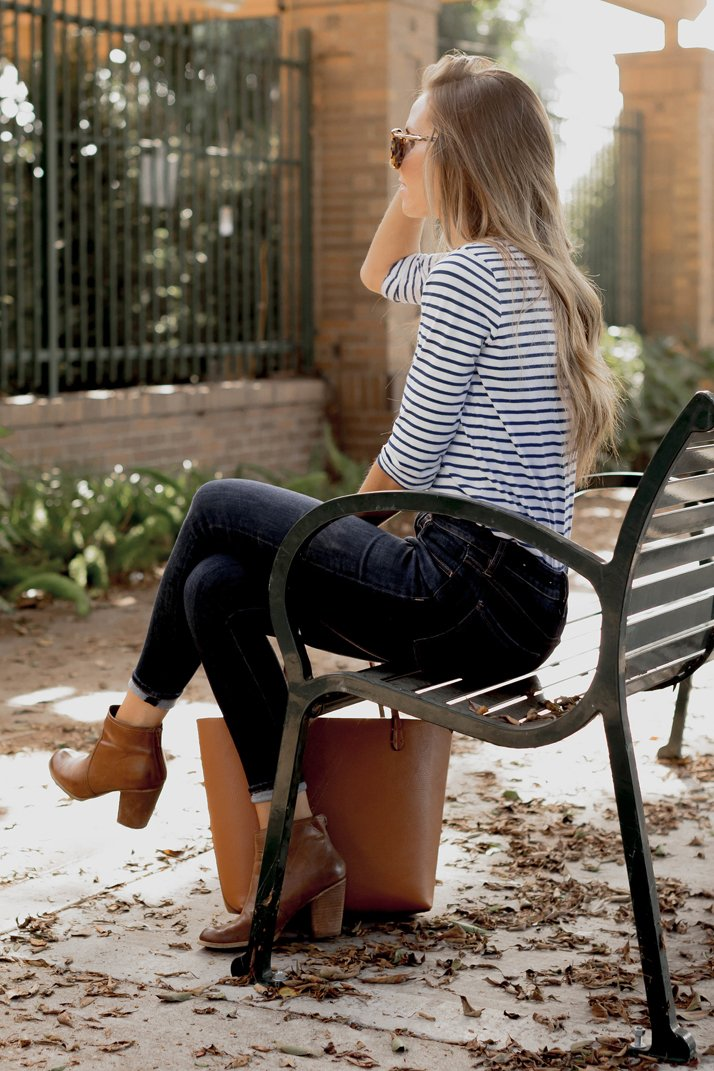 stripes, dark jeans, and cognac accessories