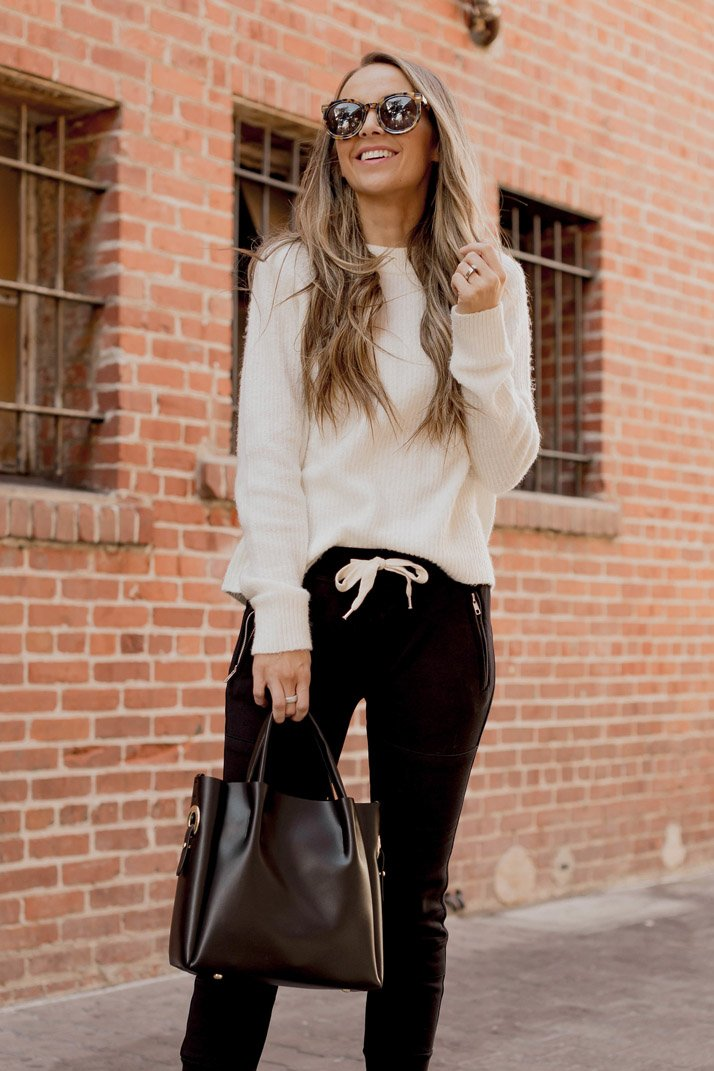 black joggers and a white fuzzy sweater