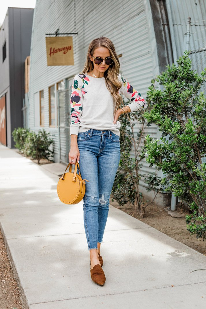 a sweater and flats with a circle bag