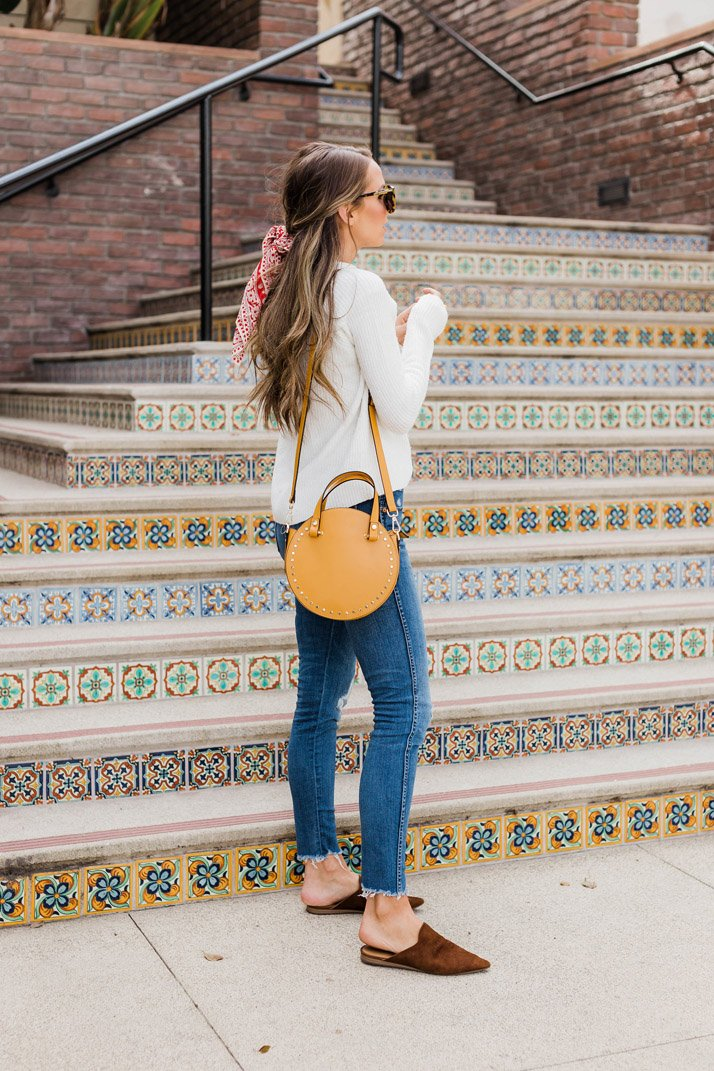 Make this really basic sweater and jeans outfit extra fun with a cool bag, a hair bandana, and some cute slides
