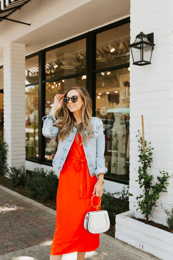 dress up this poppy red dress from everlane with a fitted denim jacket, heels, and a dressy bag