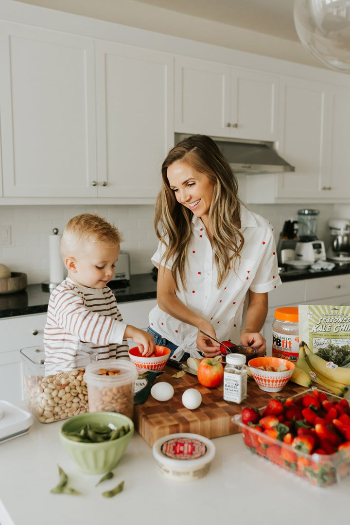 mom and son in the kitchen with healthy snacks on a cutting board