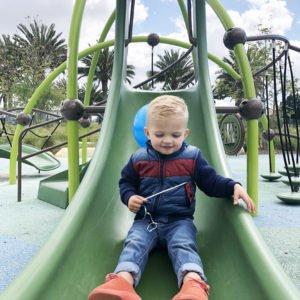 sanny sliding down the slide at the park