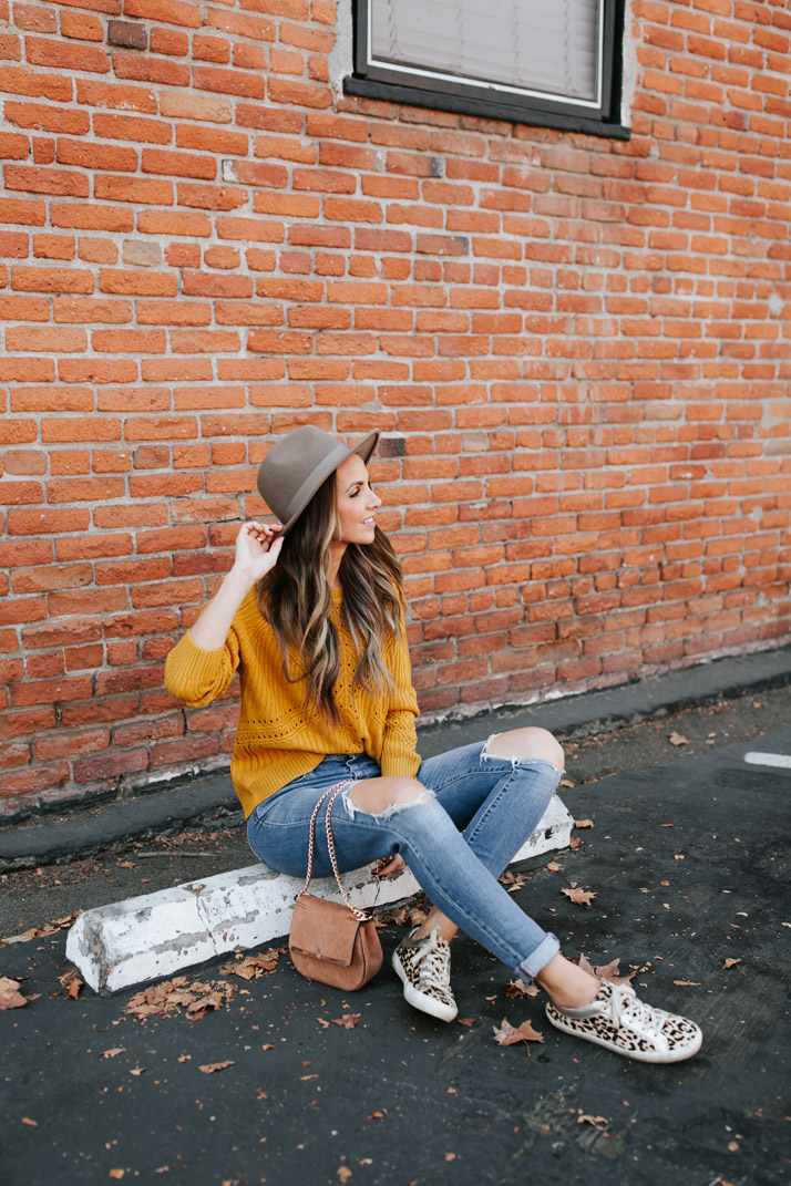 mustard yellow sweater and leopard sneakers