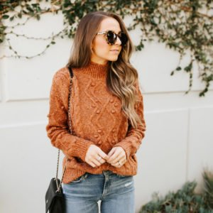 rust mock neck sweater and light wash jeans
