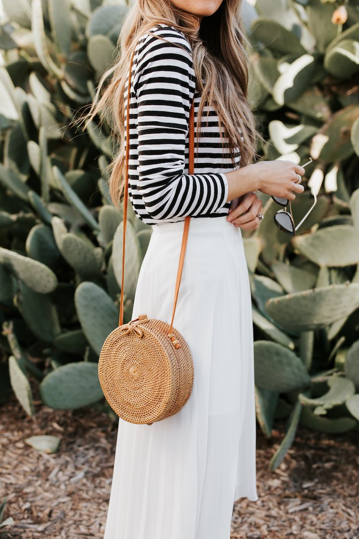 round woven bag and pleated midi skirt