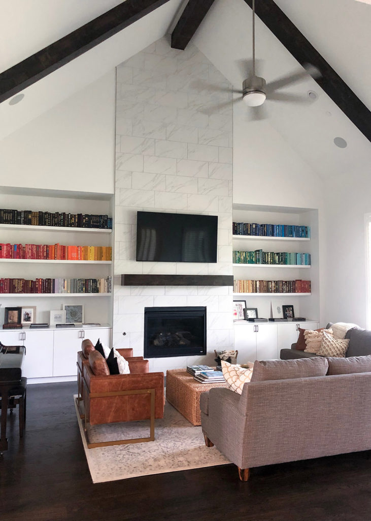 living room with fireplace and rainbow bookshelf