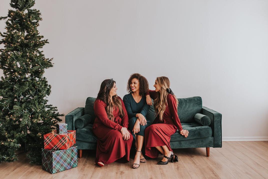 dark red midi dress dark teal midi dress girls sitting on a green velvet couch