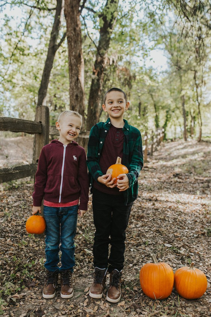 boys in fall clothes with pumpkins