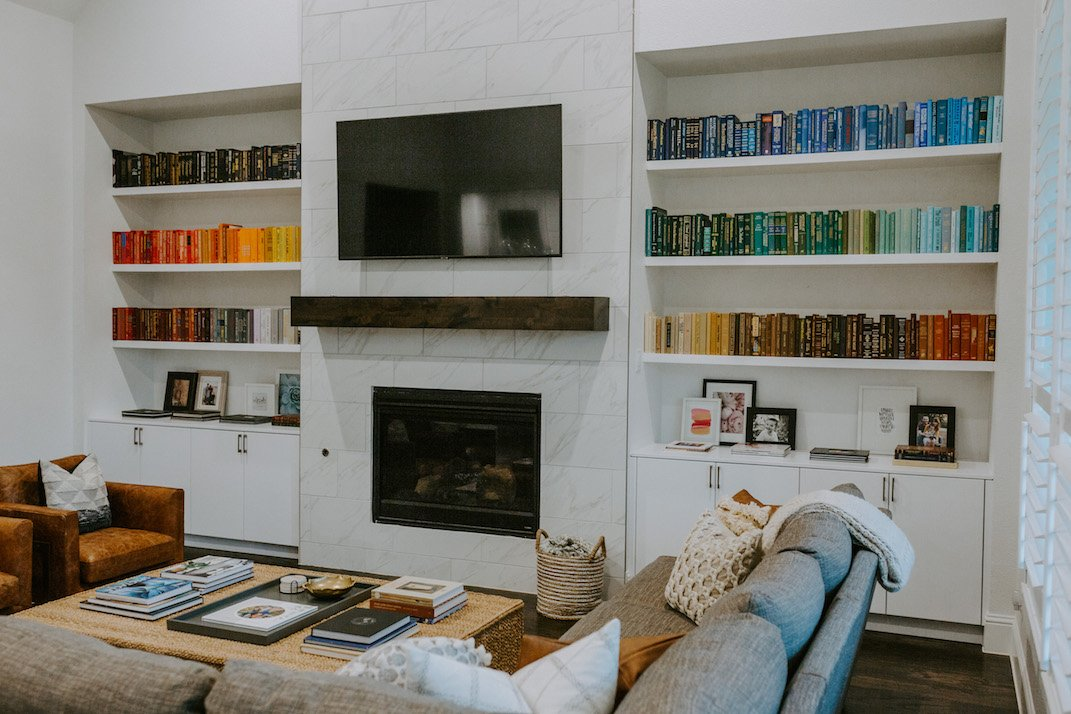 rainbow bookshelf in white floating shelves with marble fireplace