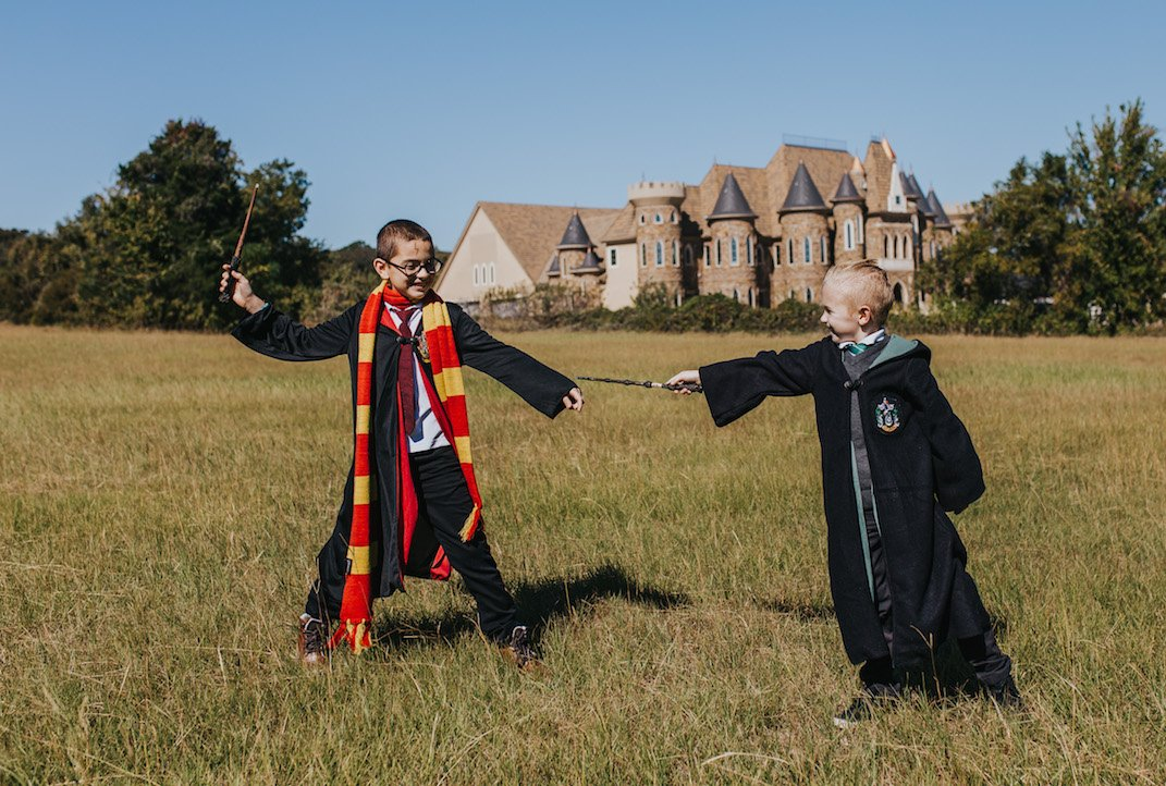 boys in a field dressed up as harry and malfoy with castle behind
