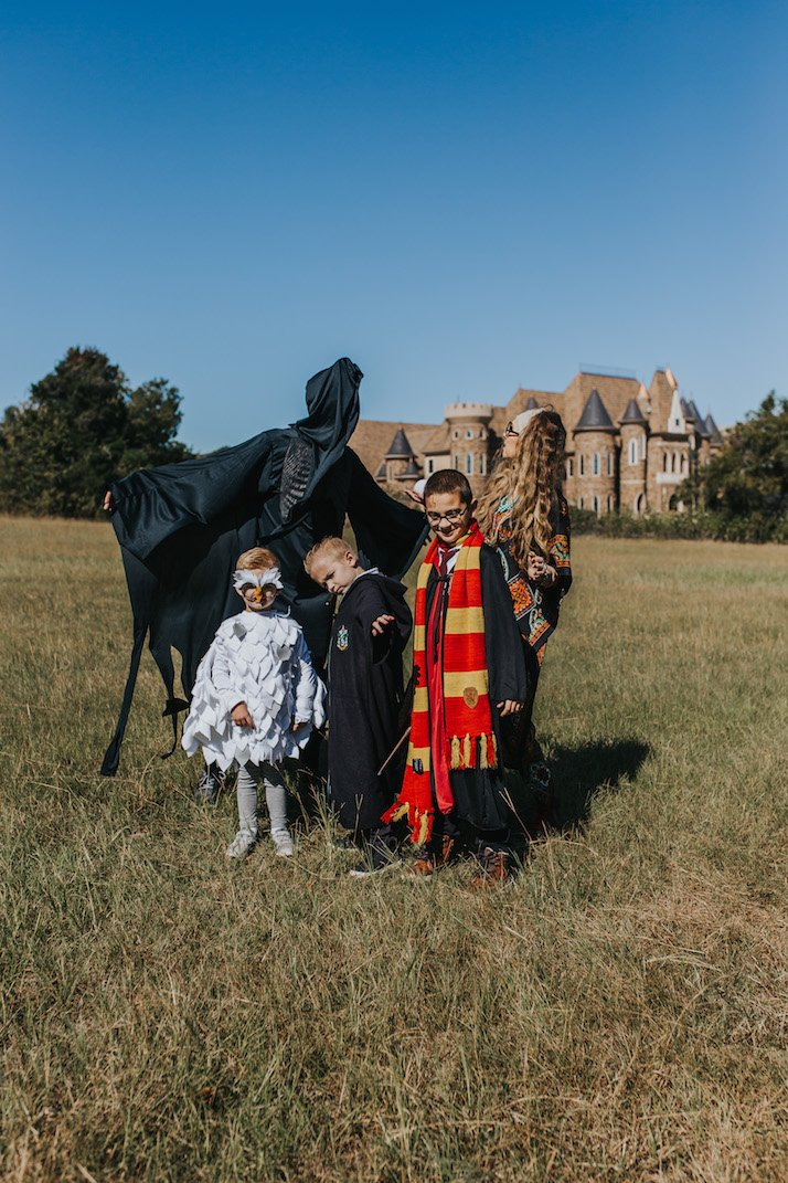 family in a field with castle dressed as harry potter