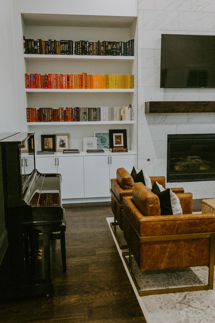 red yellow and black books in a living room with brown leather chairs