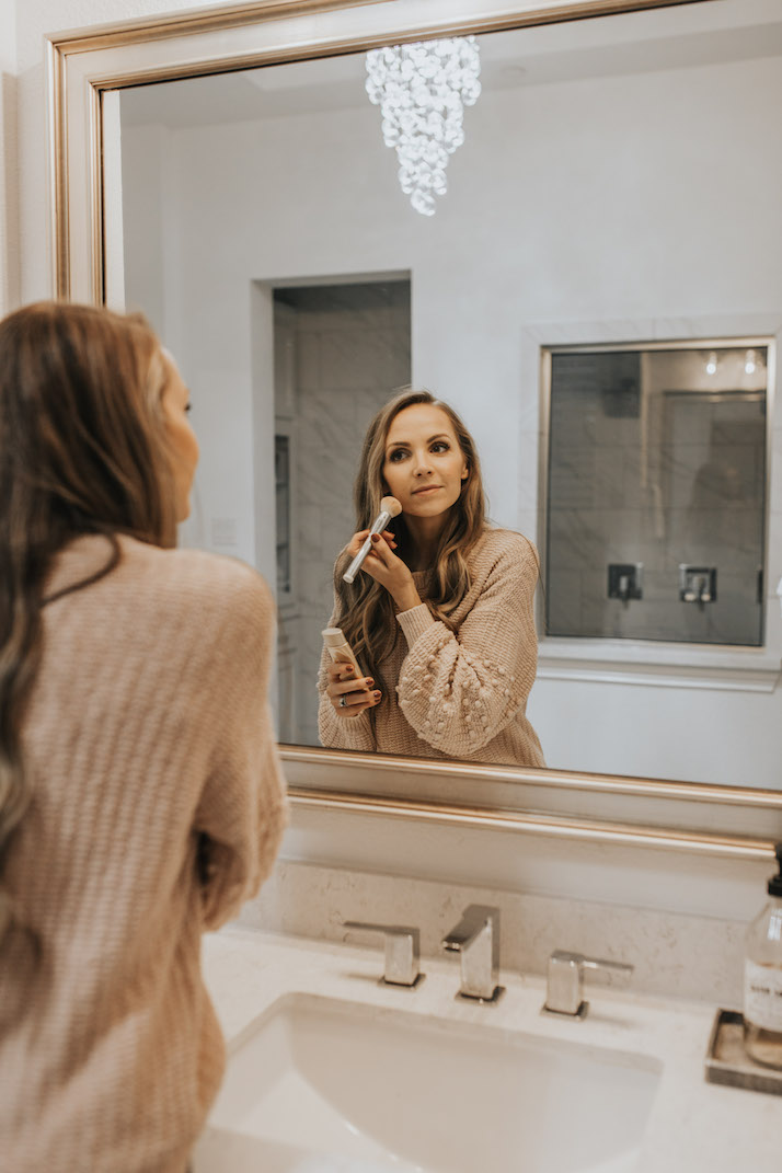 putting on makeup in a mirror with BB cream from Jane iredale