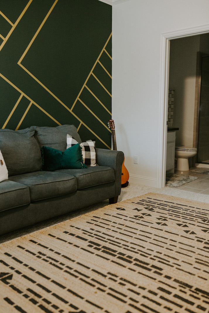 gold and green wall with blue gray couch and aztec rug