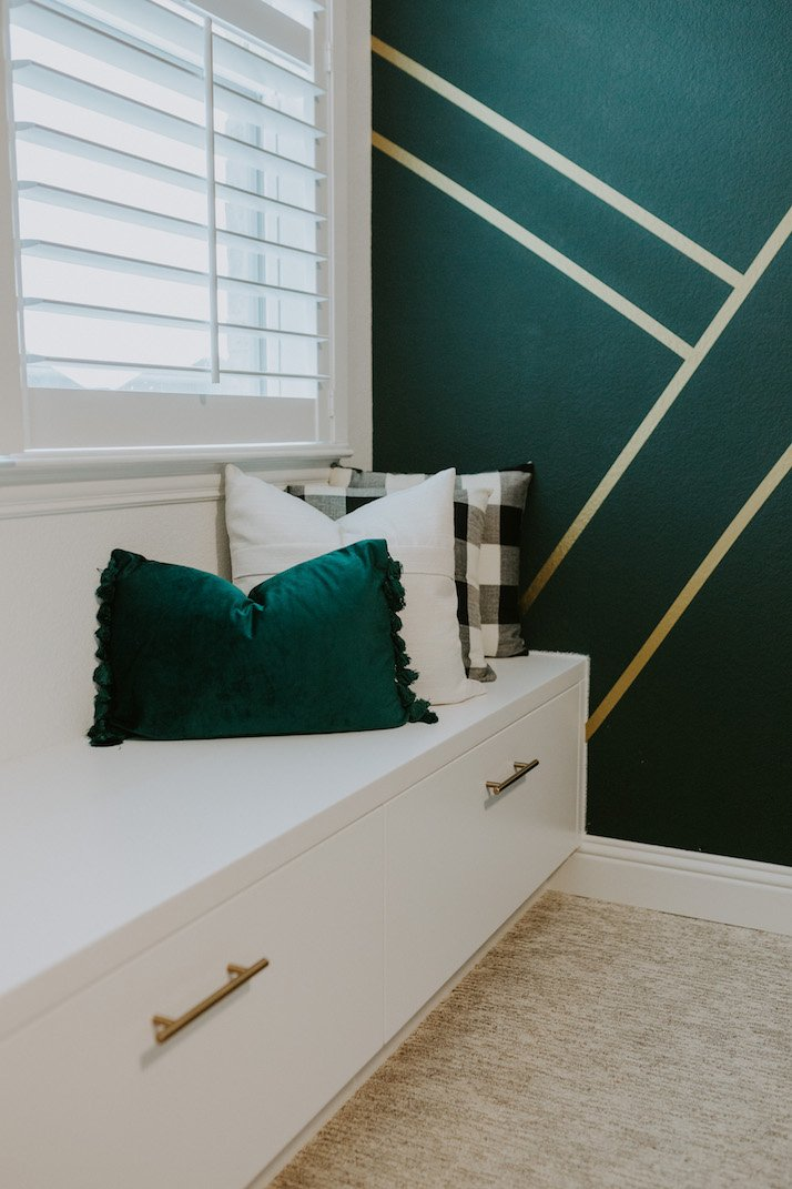 gold and green wall with white built in window seat