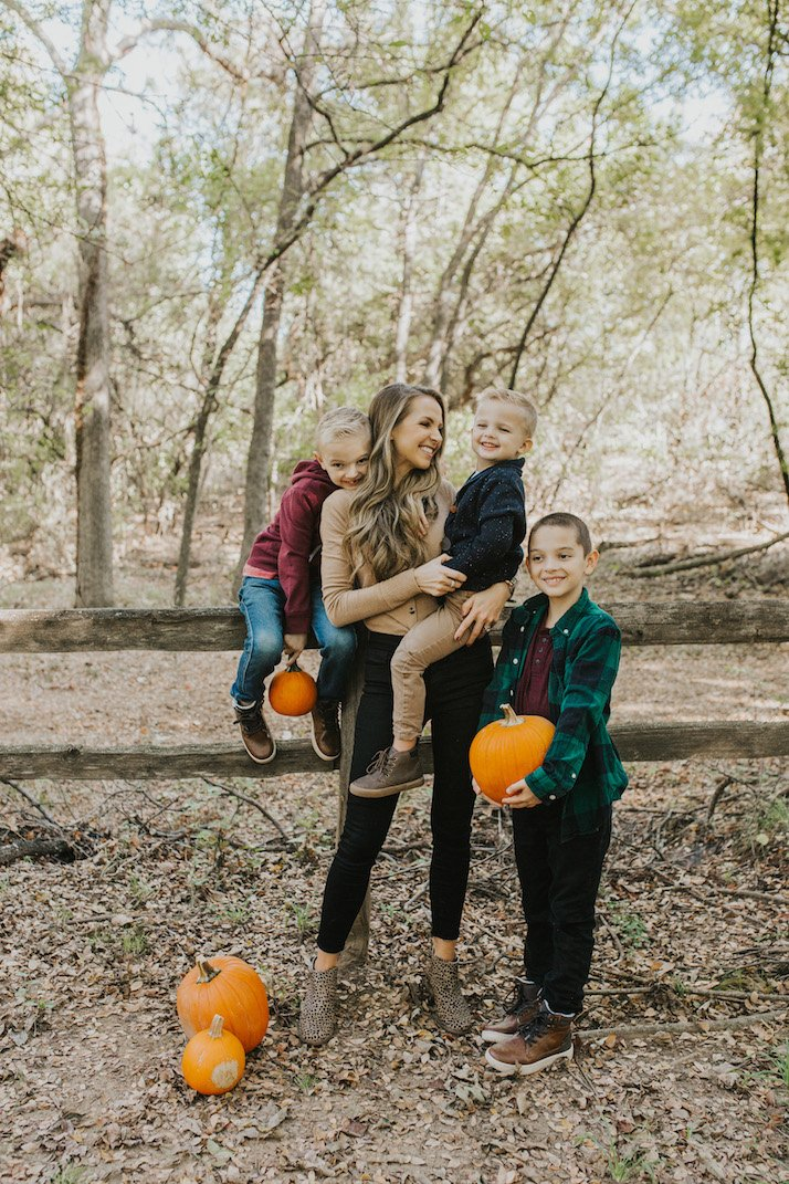 mom and sons in a pumpkin patch