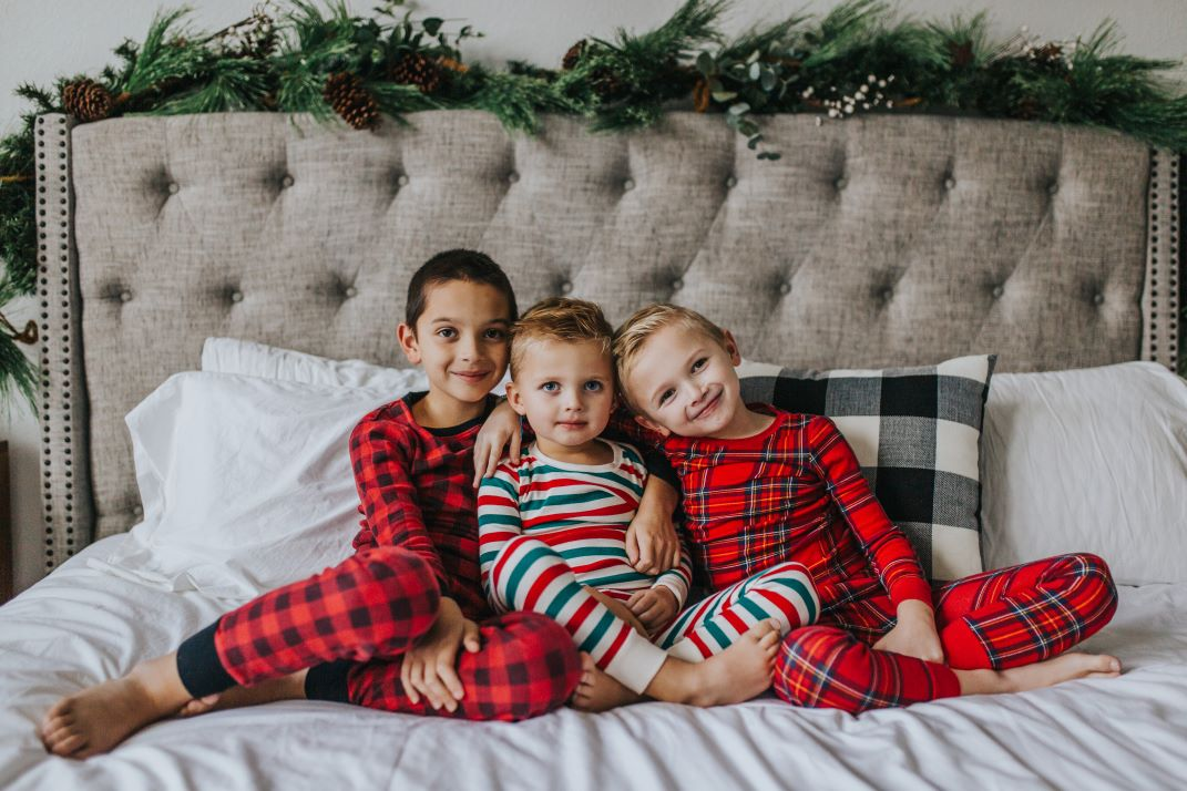 boys in christmas pajamas on the bed