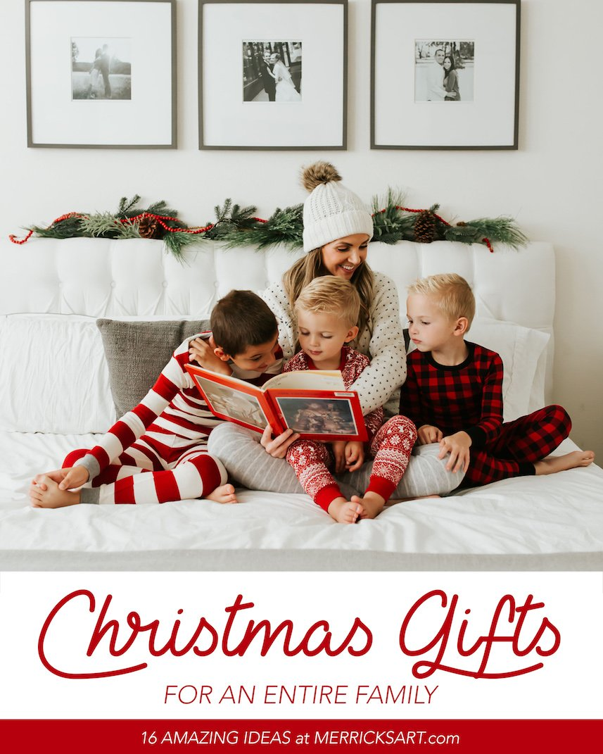 boys in red and white pajamas with mom sitting on tufted white bed