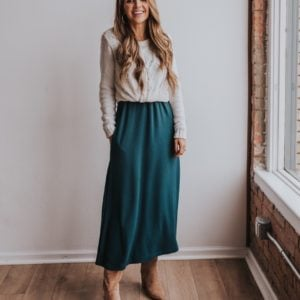 dark teal dress worn as a skirt with cable knit sweater