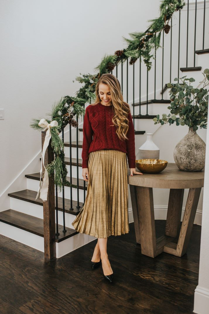 gold pleated skirt and burgundy cable knit sweater in front of curved staircase and round entry table