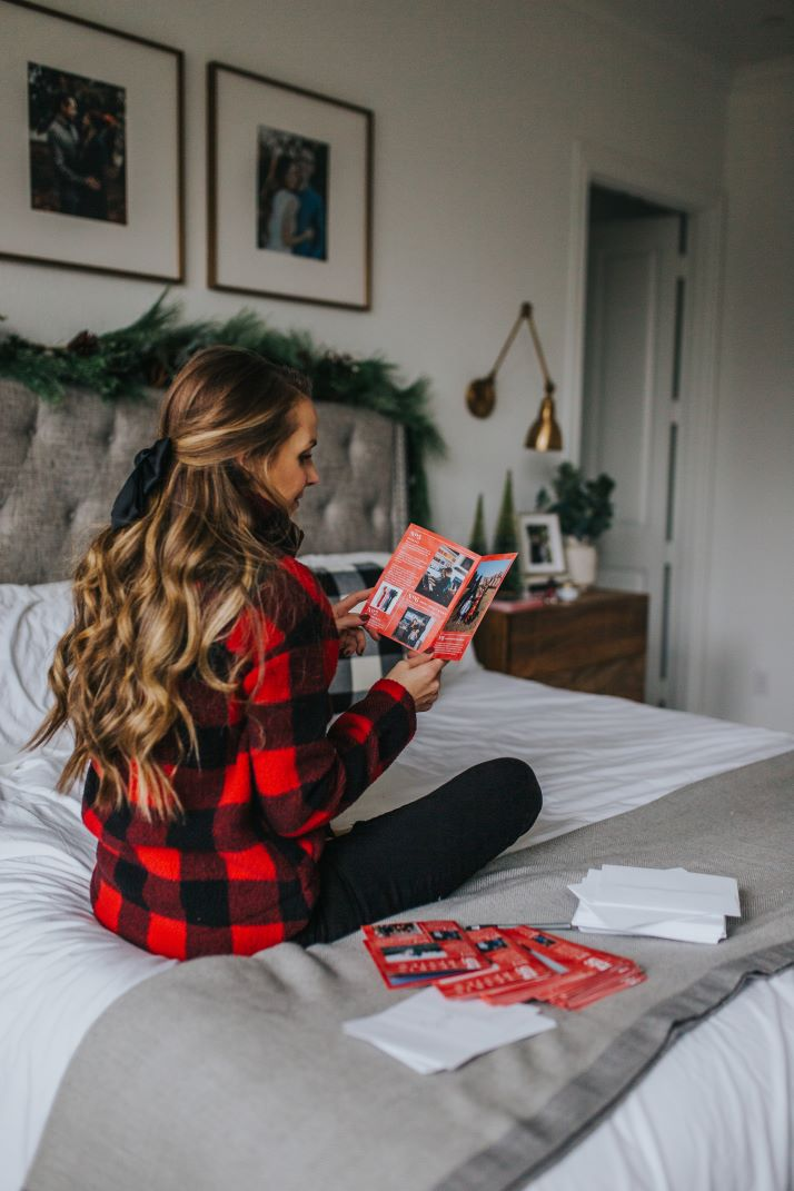 girl in buffalo check jacket on the bed with mixbook cards