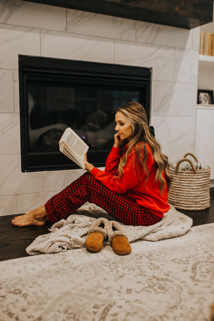 red plaid pajama pants red sweatshirt by the fireplace