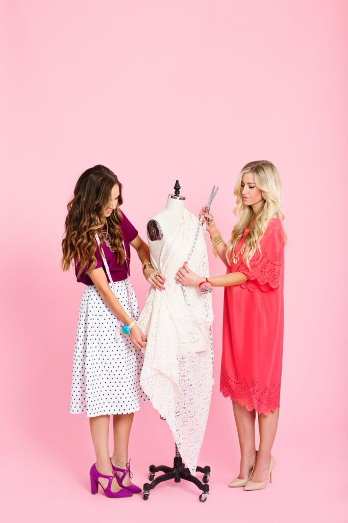 two girls with a dress form and pink backdrop
