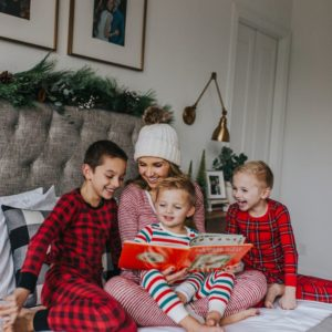 mom reading to boys on bed in christmas pajamas