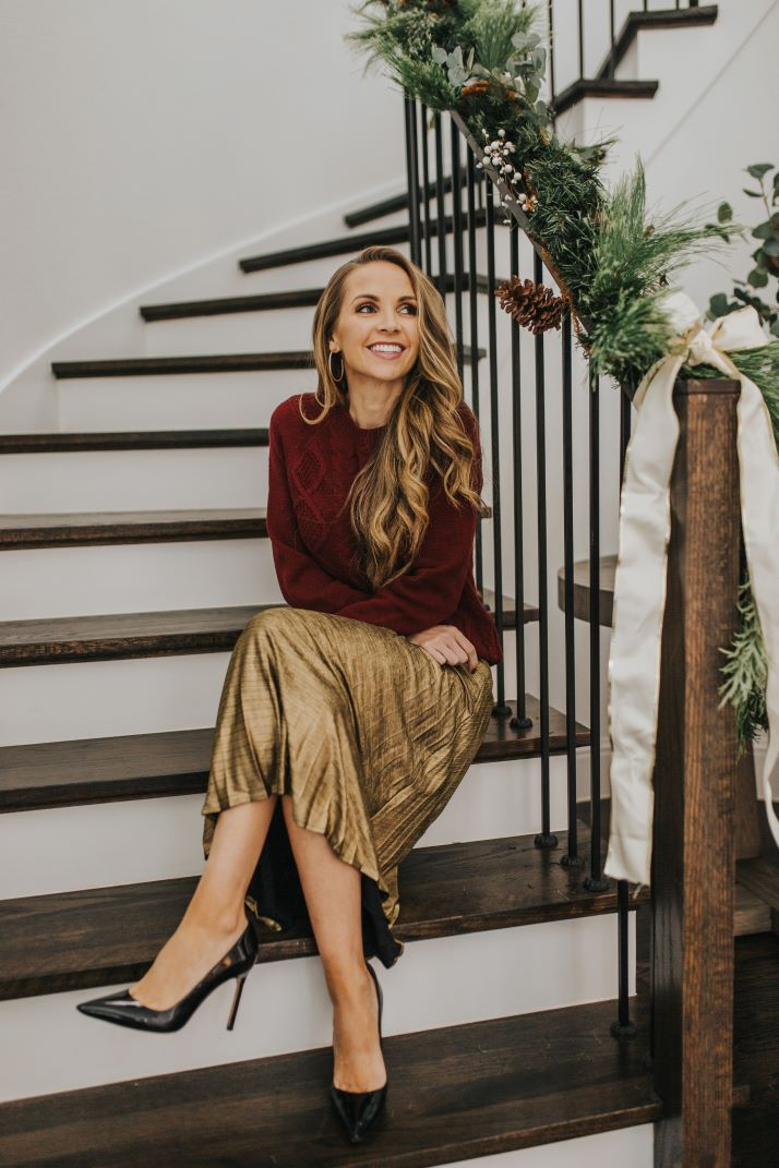 merrick on stairs with gold pleated skirt and burgundy cable knit sweater