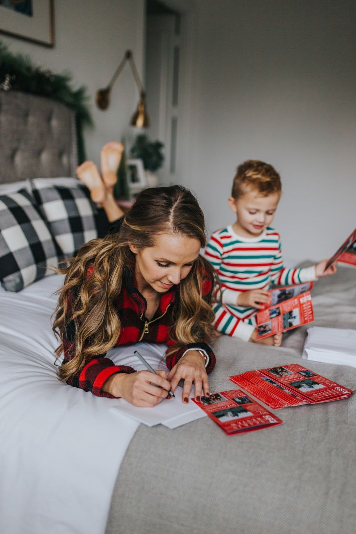 mom and son on bed prepping holiday cards