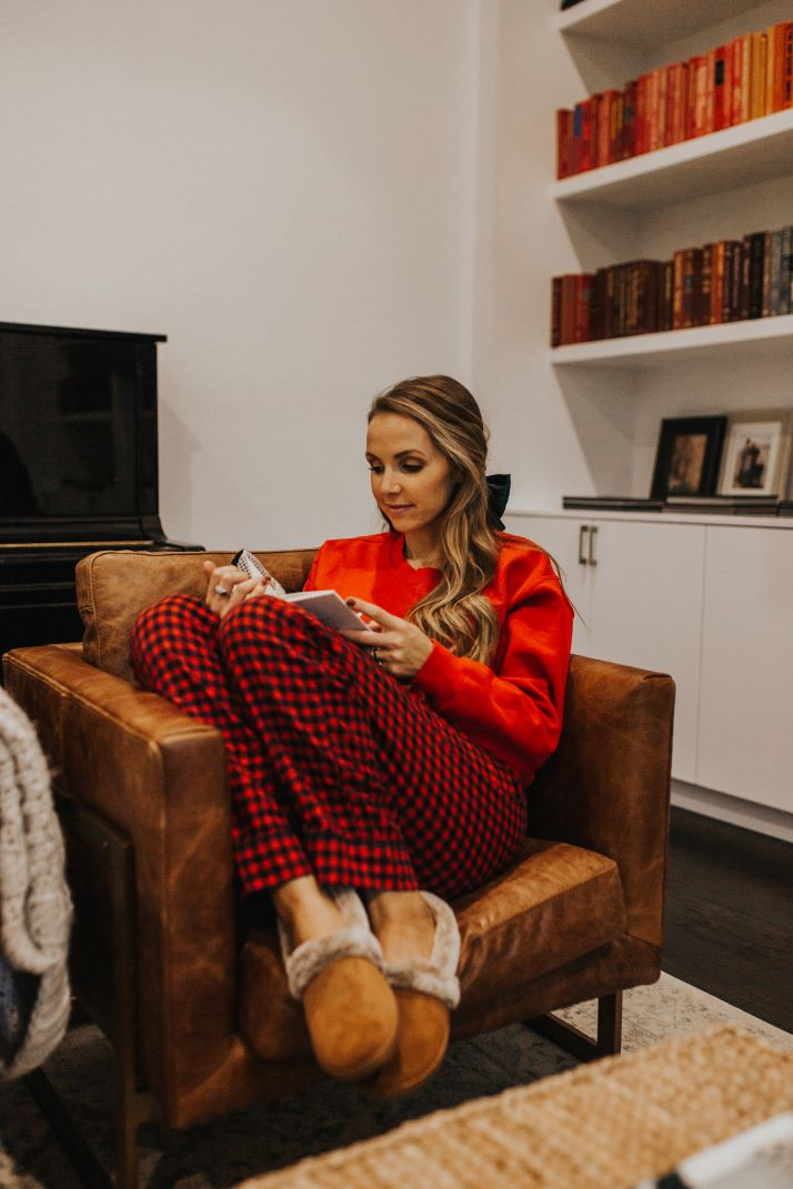 girl in red christmas pajamas sitting on leather chair reading book
