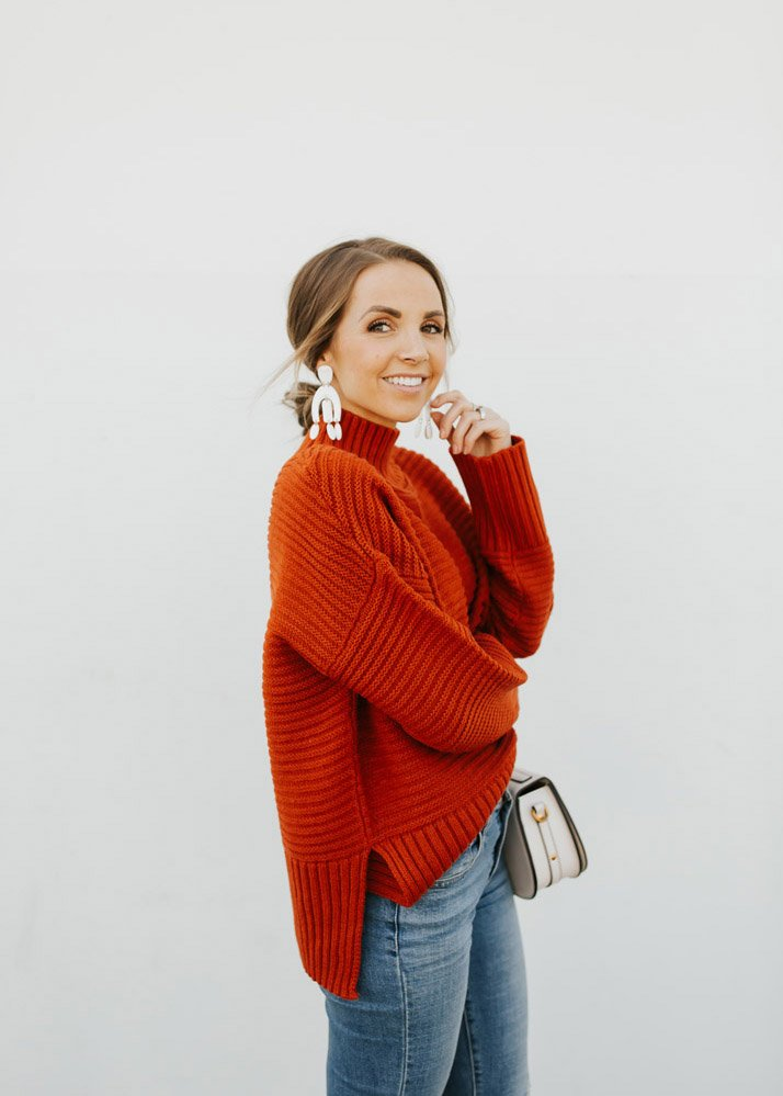 women in red sweater with arm folded
