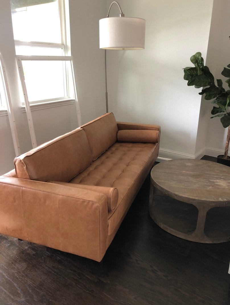 brown tufted couch with round coffee table