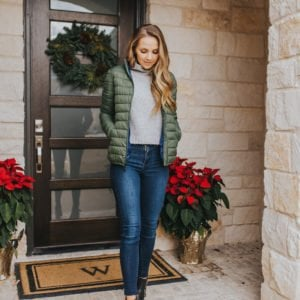 merrick on front porch with poinsettas in green puffer jacket
