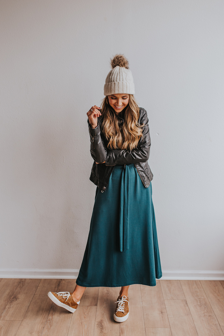 dress with leather jacket, beanie, and sneakers