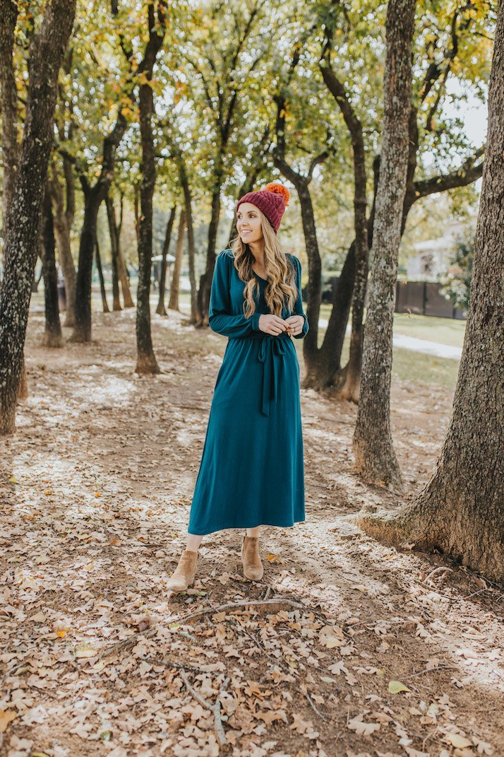 merrick in green sweatshirt dress with boots and beanie in the trees