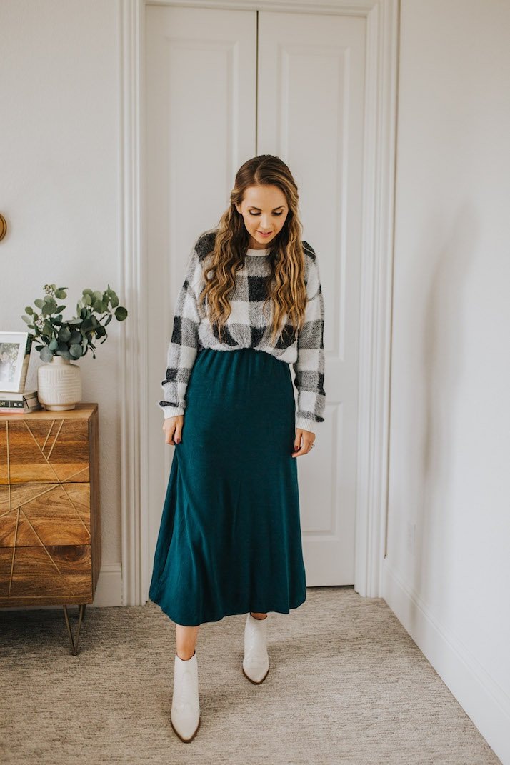 buffalo plaid sweater over a green dress with white boots