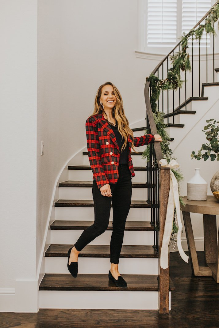 red plaid blazer and black outfit on wood stairs
