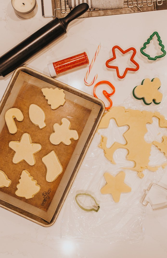 sugar cookies on a sheet pan with cookie cutters