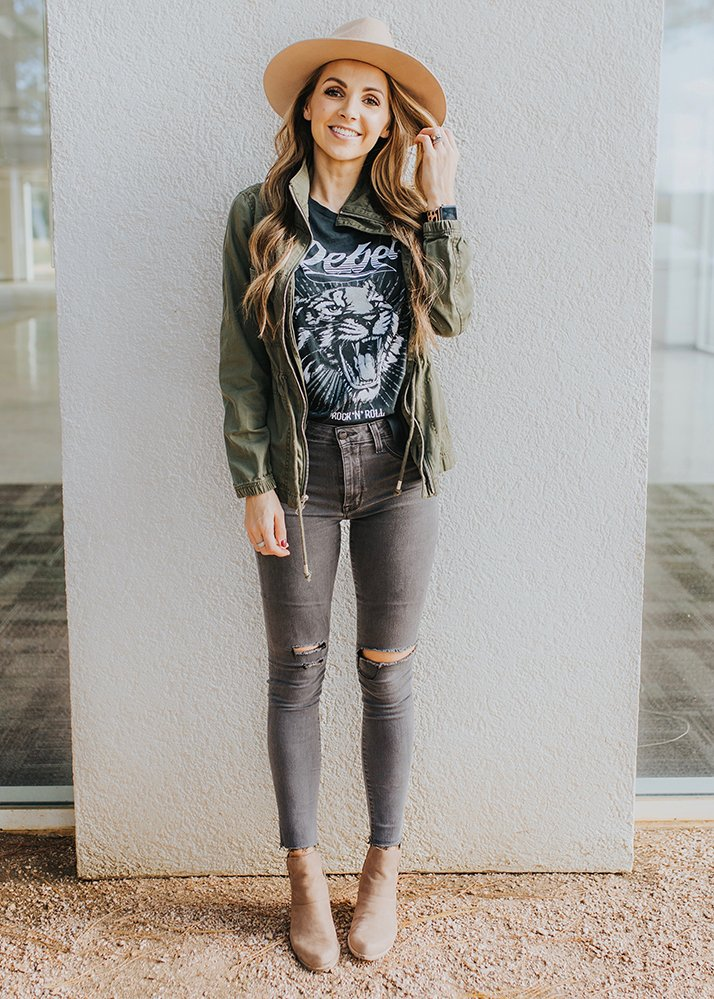 olive green utility jacket with graphic tee and jeans