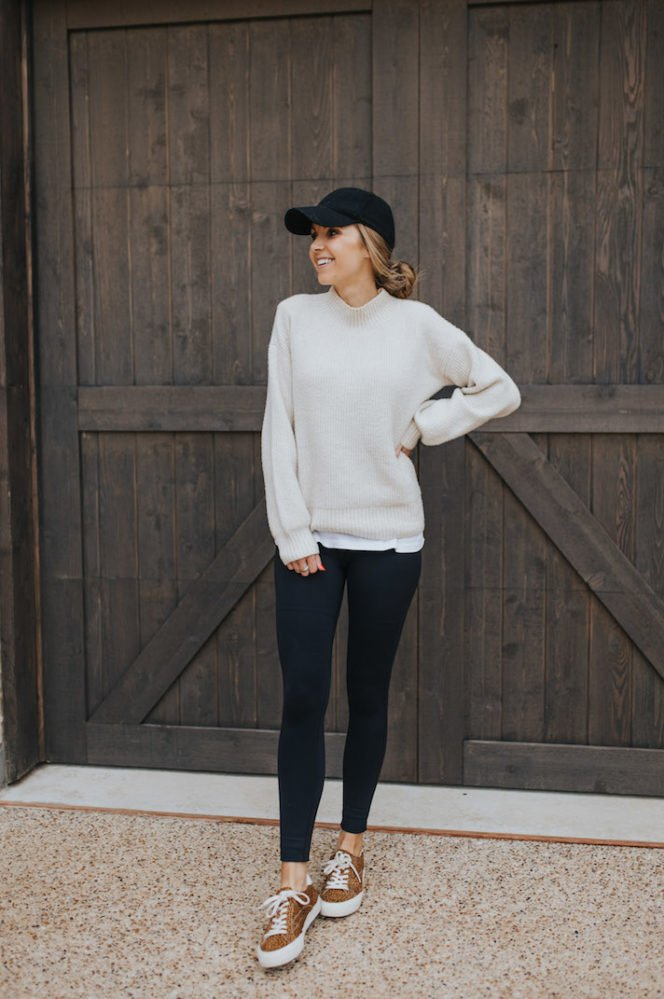 cream sweater, black leggings, black baseball cap