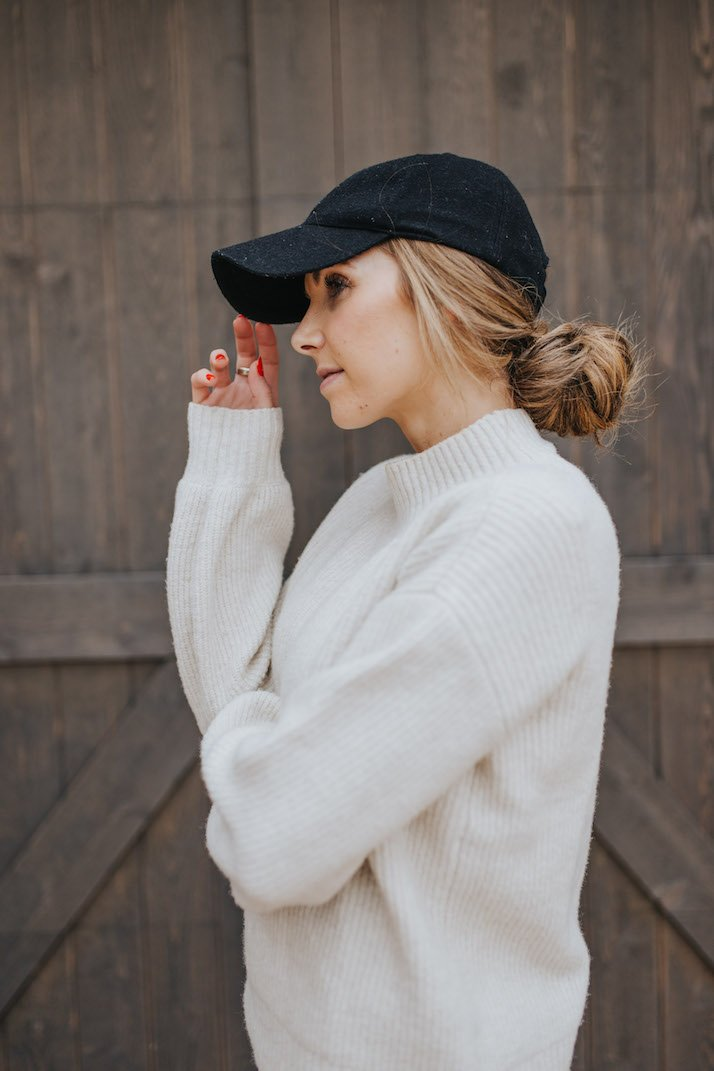cream sweater with black baseball cap