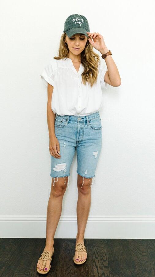denim shorts, white shirt, with a baseball cap
